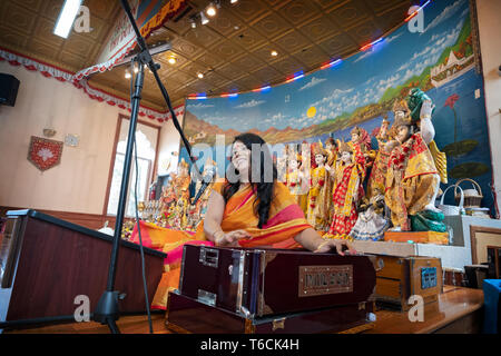 PANDITA. A female Hindu priestess sings a prayer while playing a harmonium at a temple in Jamaica, Queens, New York City. - Stock Photo