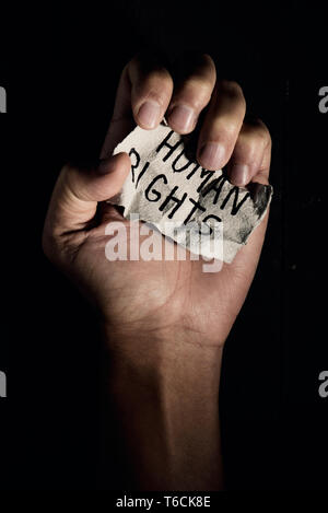 closeup of the hand of a young man with a piece of paper with the text human rights written in it, on a black background - Stock Photo