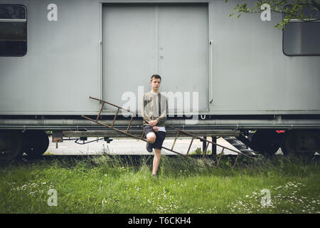 young man leaning against an old rail car - Stock Photo