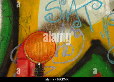 Control light in front of a wall with graffitis - Stock Photo