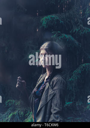 Enigmatic woman stood in dark forest - Stock Photo