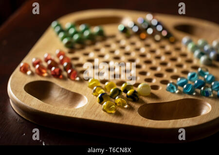 A wooden Chinese checkers game board with marbles of different colors, sitting on a cherry wood table. - Stock Photo