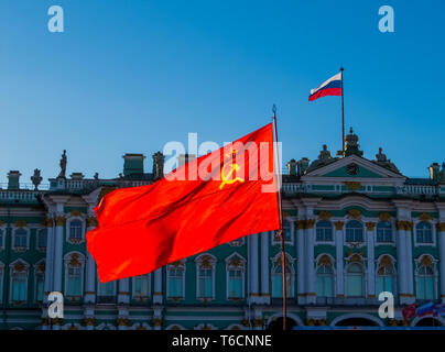 Soviet Union flag with the Russian flag and the Hermitage Museum in the background. In St. Petersburg, Russia - Stock Photo