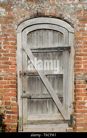 Old wooden door in brick wall - Stock Photo
