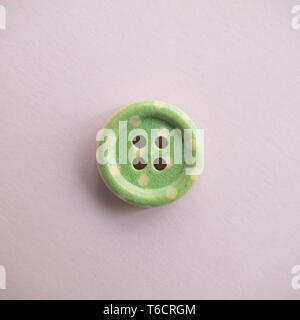 Isolated wooden button with colored colorful dots on a light pink background, sewing