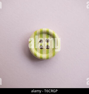 Isolated wooden button with colored colorful stripes on a light pink background, sewing