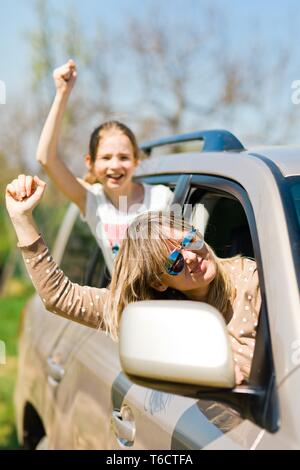 Rioters behind the wheel, female hooligans in the car showing gestures around - sport fans - Stock Photo