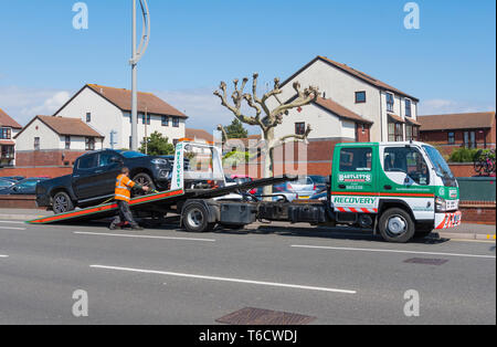 Bartletts breakdown recovery vehicle at the roadside putting a car on a trailer, in the UK. - Stock Photo