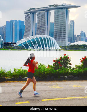 Woman jogging in Singapore bay - Stock Photo