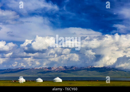 Traditional pastures in the high mountains of Kyrgyzstan. Three yurts are located on the shore of the Song Kol Lake - Stock Photo