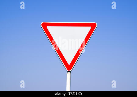 Road signs, give way. Sign on a blue background - Stock Photo