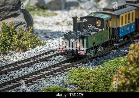 Railway modelling train outdoors on a sunny day, steam engine train - Stock Photo