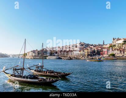 Traditional boats on Vila Nova de Gaia bank of Douro River, Porto Skyline in the background, Portugal - Stock Photo