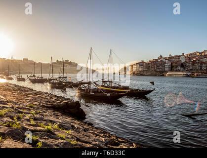 Traditional boats on Vila Nova de Gaia bank of Douro River, Porto Skyline in the background, Portugal - Stock Photo