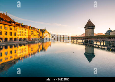 Lucerne, Switzerland. Kapellbrücke (Chapel Bridge) and water tower on Reuss river at sunrise - Stock Photo