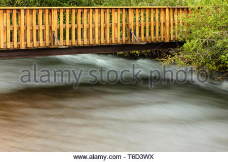 A small walking bridge crosses over the fast flowing waters of the Big Thompson River near the Spruce Lake RV Park, Estes Park, Colorado in mid-July. - Stock Photo