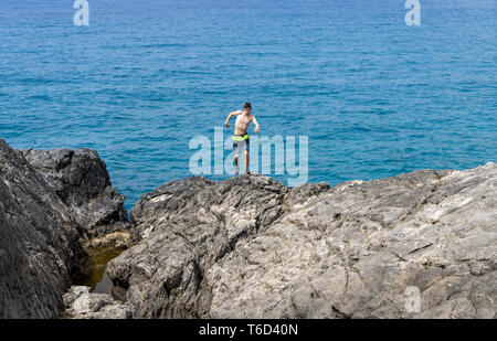 young man on a cliff getting out of balance - Stock Photo