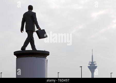 sculpture Saeulenheiliger busniessman on the top of an advertising column, Duesseldorf, Germany - Stock Photo