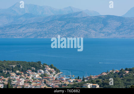 Kassiopi on the North East coast of the Greek island of Corfu in Greece with the Albanian coast in the background. - Stock Photo