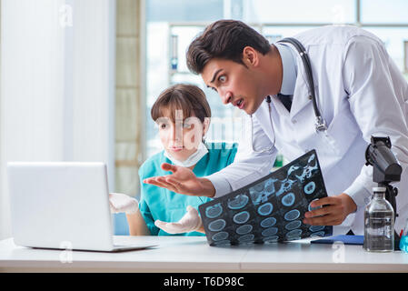 Two doctors discussing x-ray MRI image in hospital - Stock Photo
