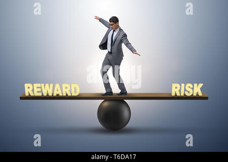 Businessman balancing between reward and risk business concept - Stock Photo