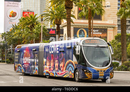 LAS VEGAS, NEVADA, USA - FEBRUARY 2019: Express bus travelling on Las Vegas Boulevard, also known as 'The Strip'. The bus is covered with advertising - Stock Photo