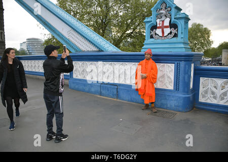 Buddhist monk having his picture taken on Tower Bridge, London UK April 2019 - Stock Photo