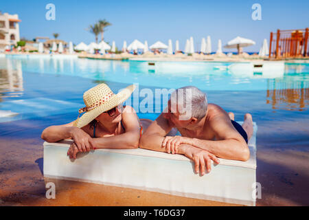 Senior couple relaxing in swimming pool lying on chaise-longue. People enjoying summer vacation. - Stock Photo