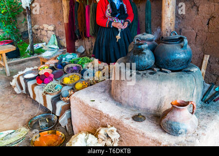 Inca woman and the simple equipment for natural dyeing wool process at Cusco in Peru - Stock Photo