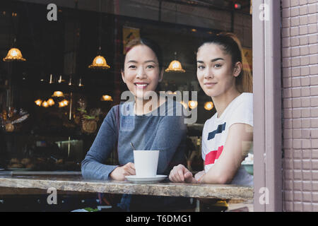 View through window of Mum and daughter sitting in cafe with coffee mug. - Stock Photo