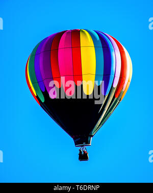 Beautiful Black and Rainbow Hot Air Balloon over Bend Oregon - Stock Photo