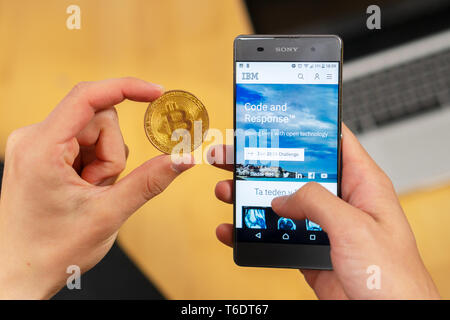 SLOVENIA - MARCH 29, 2019: IBM - International Business Machines Corporation website on a smartphone and businessman trader holding Bitcoin. - Stock Photo