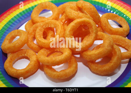 Onion ring crisps on a rainbow paper plate - Stock Photo