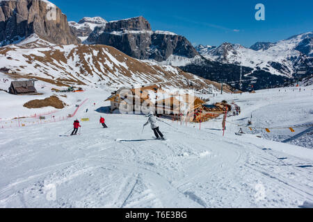 Skiers on the piste of the Val Di Fassa valley on the Dolomites ski slope - Stock Photo