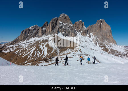 Skiers on the piste op the Val Di Fassa valley on the Dolomites ski slope - Stock Photo
