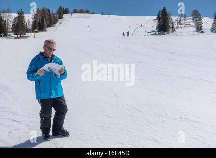 skier man reading a piste map on the ski slope - Stock Photo