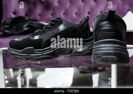 A pair of black trendy sneakers on the background of a glass table and a purple sofa - Stock Photo