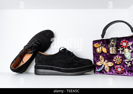 pair of black fashionable boots with thick soles and a purple velvet bag adorned with animals made of rhinestones on a white background - Stock Photo