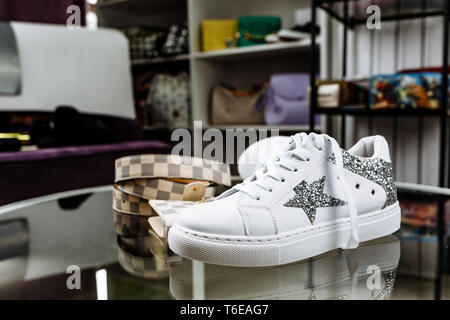 white fashionable sneakers decorated with stars of sequins, a checkered belt and a purse on a glass table against the background of shelves with bags - Stock Photo