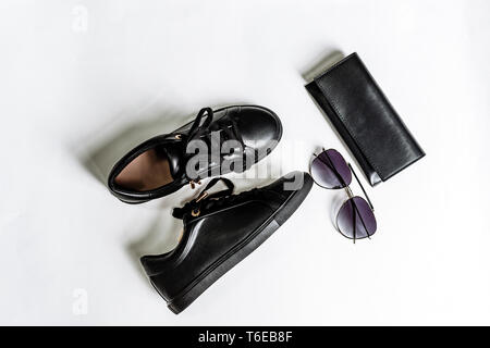 fashionable black shoes, purse and sunglasses with black lenses on a light background - Stock Photo