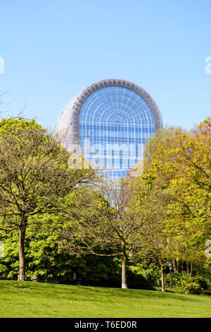 The glass roof of the Paul-Henri Spaak building, seat of the European Parliament in Brussels, sticking out above the trees of the Leopold park. - Stock Photo