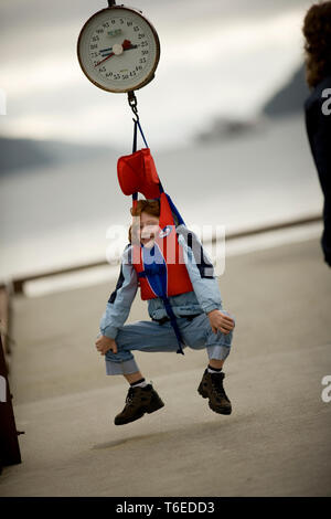 Young girl hanging from a fish weigh. - Stock Photo