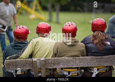 Group of people wearing red helmets sitting next to each other on a wooden bench outdoors. - Stock Photo