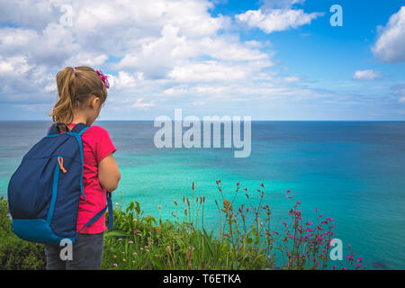 Girl with a backpack on the Cornish coast - Stock Photo