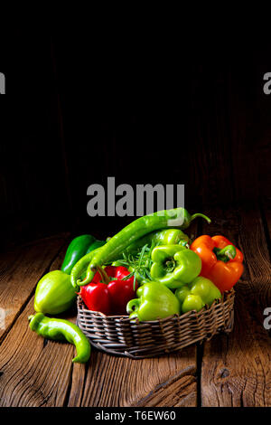 various harvested peppers and hot peppers in basket - Stock Photo