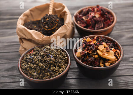 Different types of dry tea leaves on table - Stock Photo