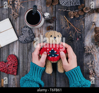 women's hands in a green sweater are holding an old teddy brown bear, on a wooden table is a cup with black coffee and decor, top view - Stock Photo