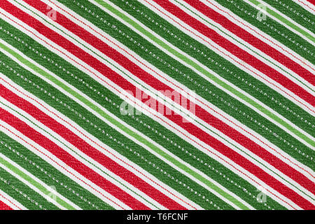 Red, white & green striped Christmas cloth laying flat for background and texture with the stripes in diagonal direction - Stock Photo