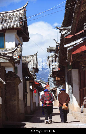 Lijiang, Yunnan province, China : Two women walk past traditional Naxi architecture in the Old Town of Lijiang, a national historical and cultural cit - Stock Photo