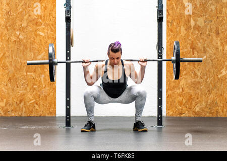 Young girl doing a back squat with a barbell weight resting across the back of her shoulders in a gym - Stock Photo